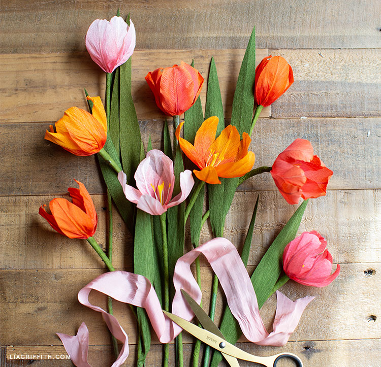 ombré crepe paper tulips with pink ribbon on floor