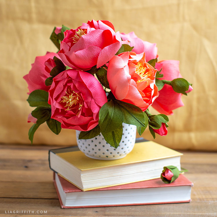 crepe paper peony flowers in vase on stack of two books