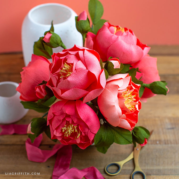 pink crepe paper peonies and buds next to empty white vases, pink ribbon, and gold scissors