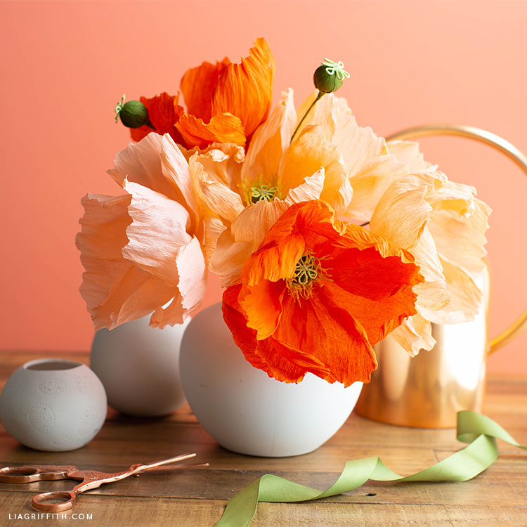crepe paper poppies and buds in white vase next to scissors, small empty pot, green ribbon, and gold watering can