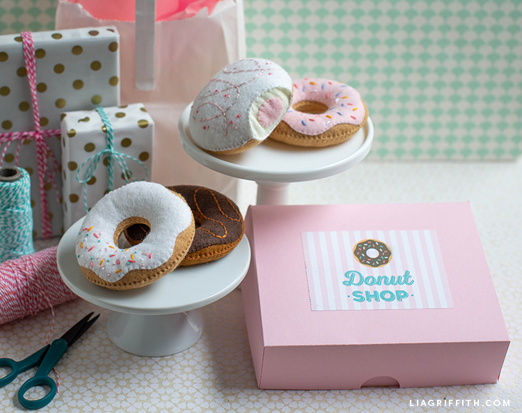 felt donuts on donut stand next to wrapped gifts, donut box, twine, and scissors