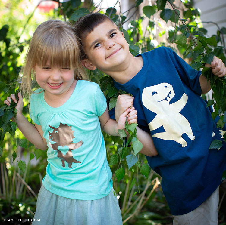 Girl and boy wearing dinosaur shirts outside