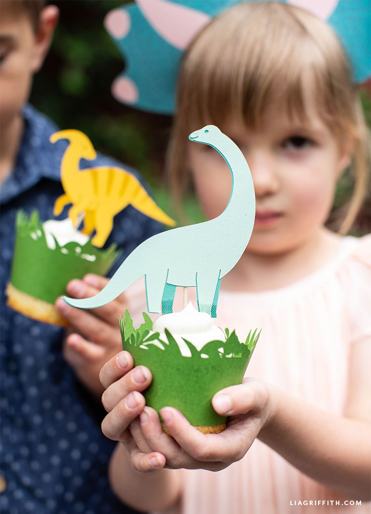 Little girl holding cupcake with dinosaur topper