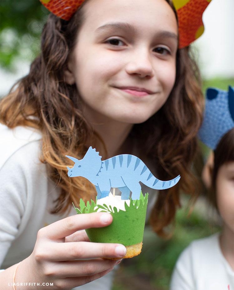 Little girl holding dinosaur cupcake