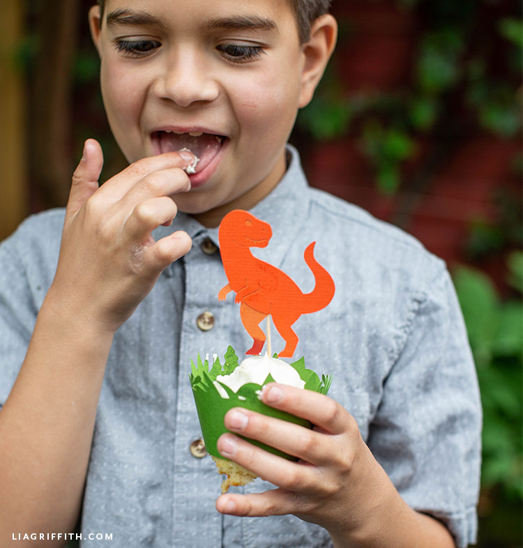 Little boy licking frosting from dinosaur cupcake