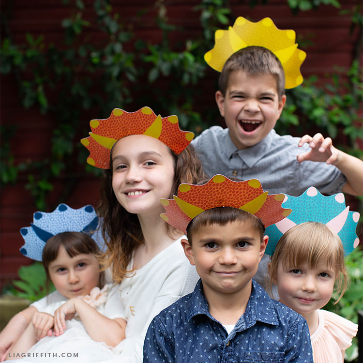 group of kids wearing dinosaur headbands for party
