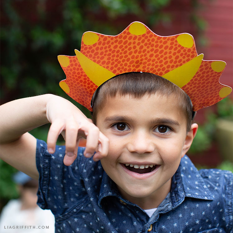 little boy wearing triceratops party hat