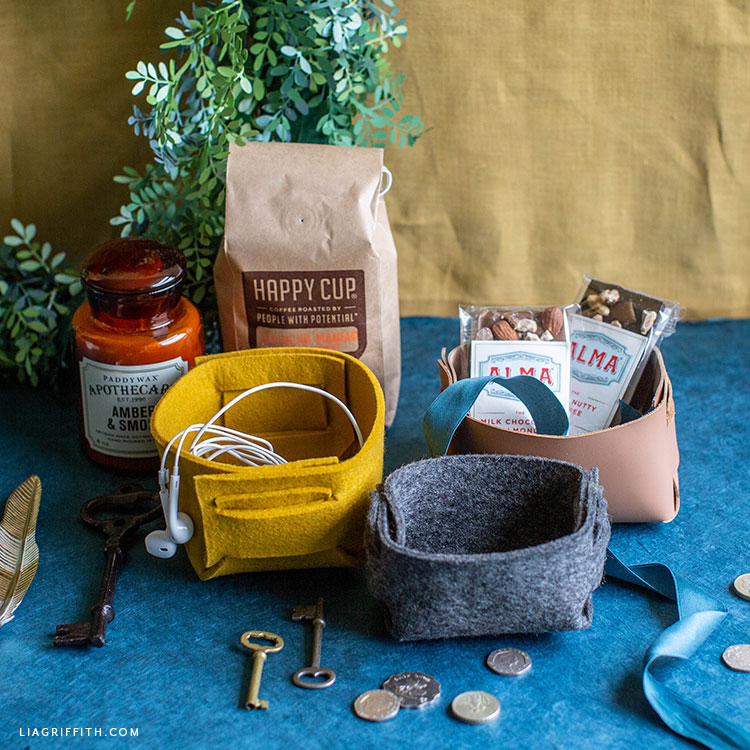 felt and leather baskets with candle, coffee, chocolate bars, headphones, keys, and coins