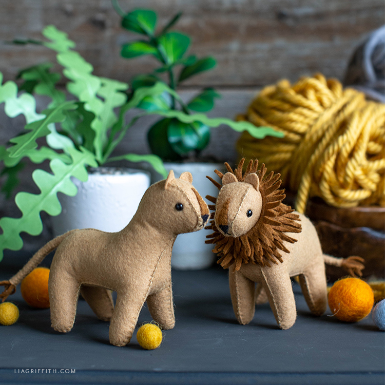 felt lion and lioness next to paper plant and yarn
