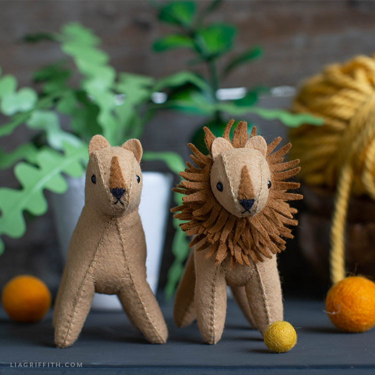 felt lion and felt lioness in front of paper zig-zag plant and yarn