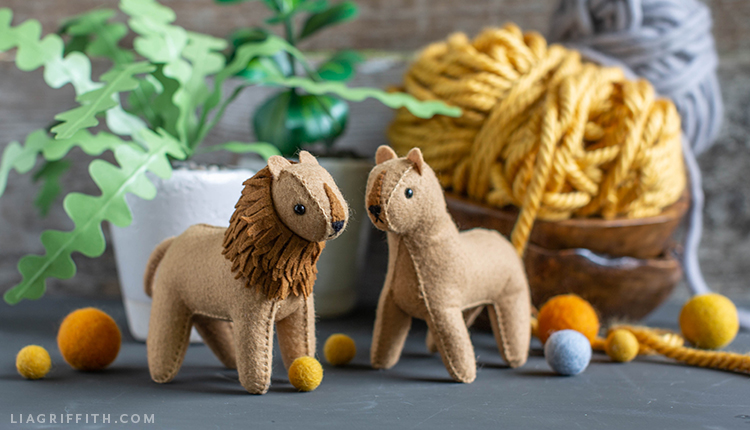 felt lion and lioness in front of paper zig-zag plant with yellow and grey yarn