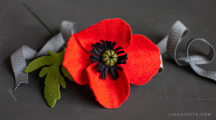 felt red poppy with black and white ribbon
