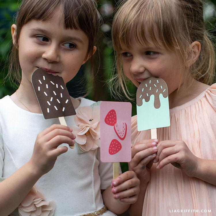 Two little girls pretending to eat papercut ice cream bars