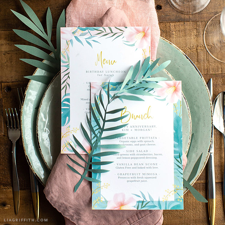 tropical menus on plates with napkins, silverware, and paper fern leaves