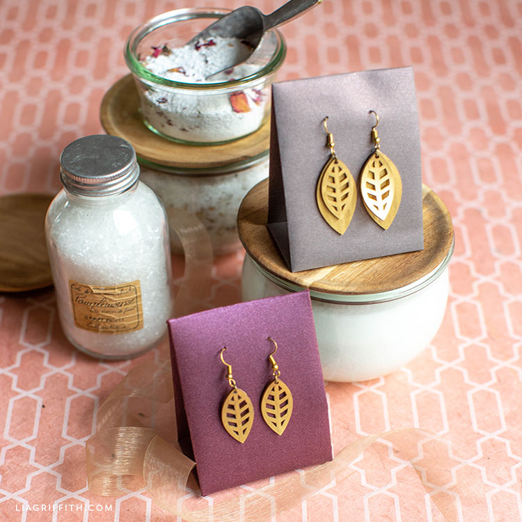handmade earrings in earring holders on top of bath products