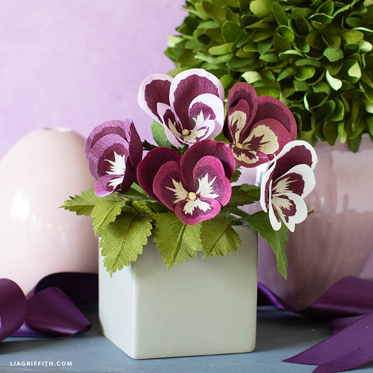 purple crepe paper pansies in small grey container in front of crepe paper topiary