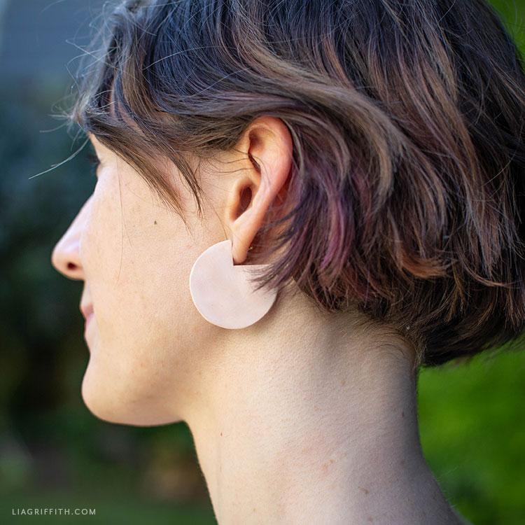 woman wearing geometric clay earrings