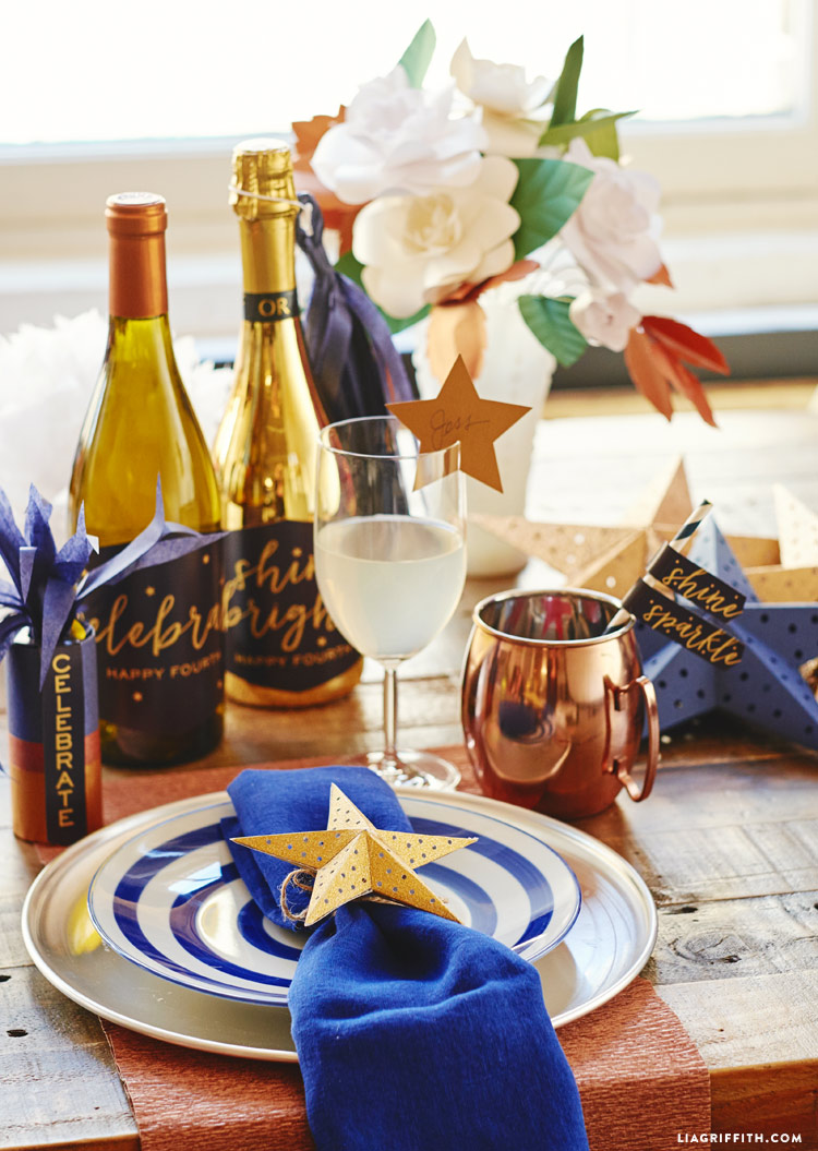 Table setting with 3D paper star on napkin, paper star on drink, paper gardenia bouquet, tissue paper firecrackers, and wine bottles with happy fourth labels