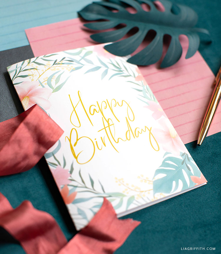tropical happy birthday card with envelope liners, red ribbon, and paper monstera leaf