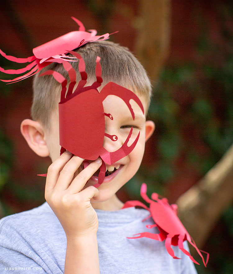kid laughing with paper crabs