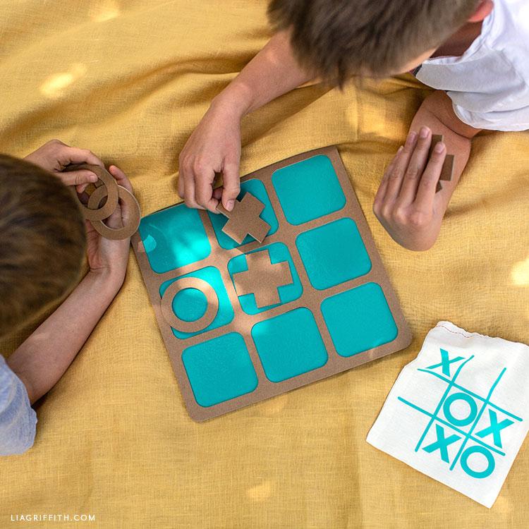 Kids playing travel tic-tac-toe game