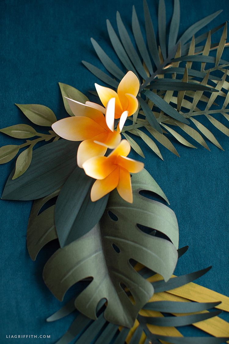 frosted paper plumerias with paper monstera leaf and palm leaves