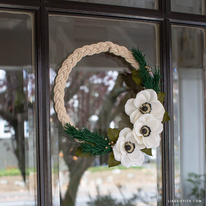 handmade braided rope wreath with crepe paper anemones and holiday greens
