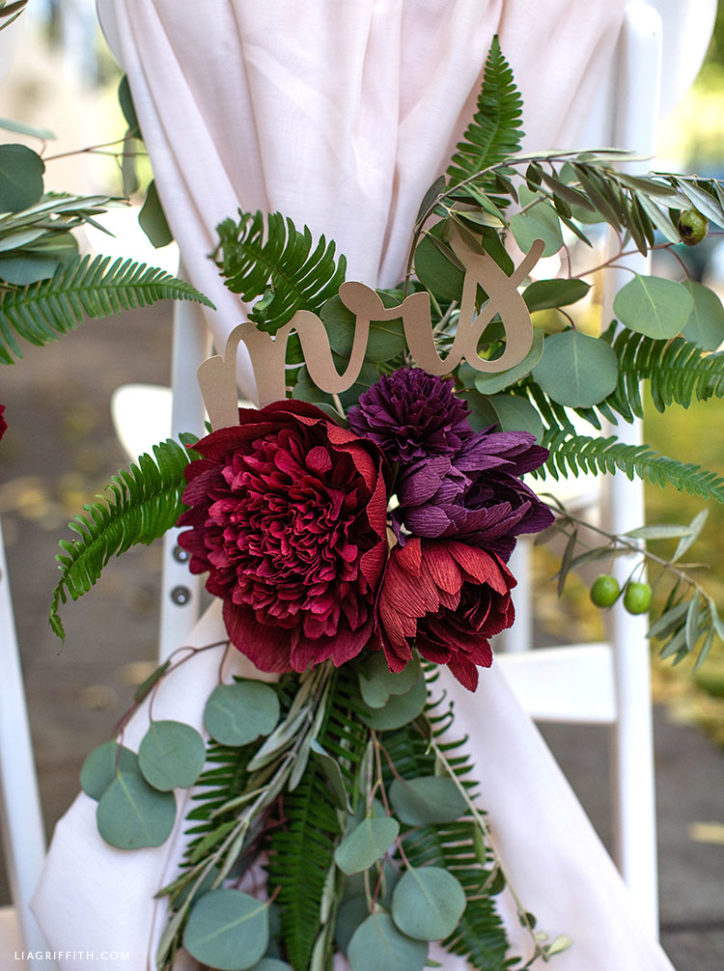 wedding chair decorations featuring crepe paper fall flowers, fresh greenery, and mrs. sign