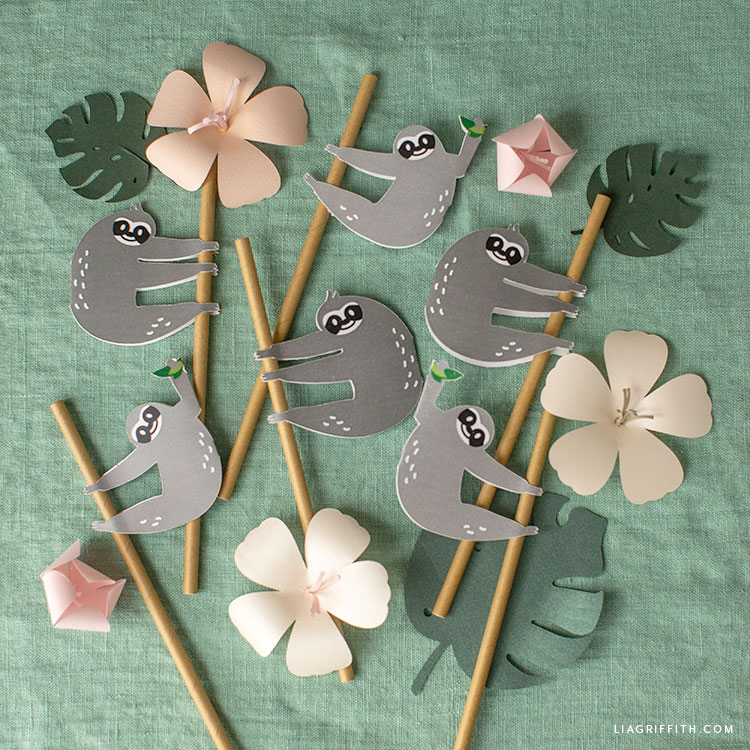 sloth straw huggers with paper flowers and monstera leaves